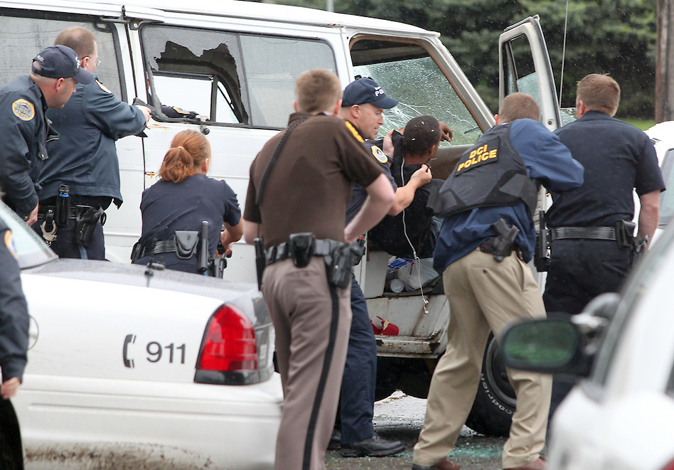 Law enforcement officers pull a robbery suspect from a van  near the 1900 block of Hubbell Avenue following a bank robbery and carjacking May 13 in Des Moines. (Christopher Gannon/The Register)