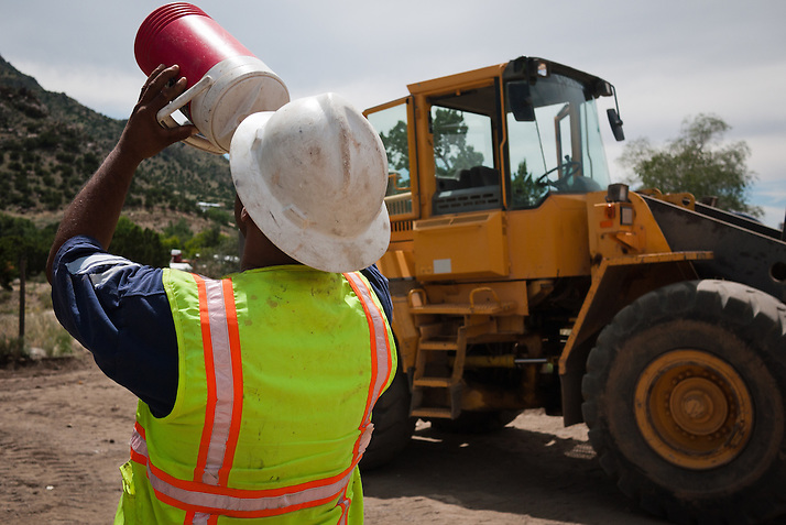 A laborer gulps water after another day at work under the hot sun as part of the Carnuel Water Systems Improvement Project on Friday August 27, 2010. The $3.4 million project is supported by $2 million from the American Recovery and Reinvestment Act and will provide clean water to hundreds of Bernalillo County residents. (Steven St. John)