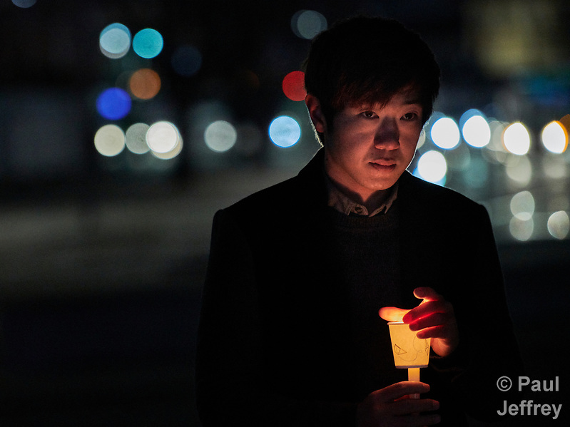 "Baek Seunghoon, a member of the Methodist Church, holds a candle during a December 7, 2017 nighttime vigil in Gwangwha-Mun Square in Seoul, South Korea. The ecumenical Advent vigil was part of ""A Light of Peace Campaign"" for the denuclearization of the Korean Peninsula, sponsored by the World Council of Churches and the National Council of Churches of Korea. (Paul Jeffrey)"