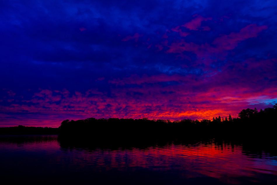 The day's first light reflects off clouds and water's surface at Serpent Lake near Deerwood, Minnesota. (Christopher Gannon)