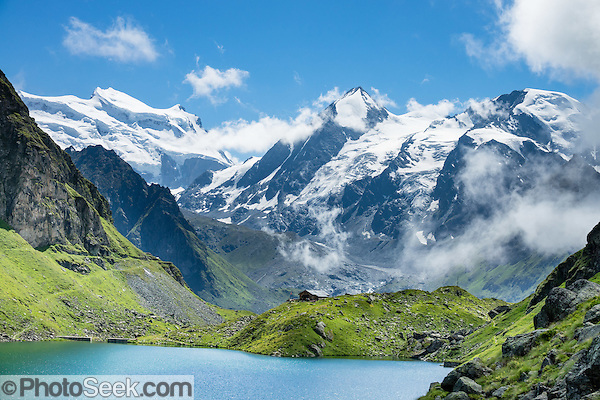 The peaks of Grand Combin (4314 metres / 14,154 feet on left), Combin de Corbassière (center), and Petit Combin (right) rise above Cabane de Louvie hut on Lake Louvie in the Pennine/Valais Alps, Switzerland, Europe. Optionally stay overnight in dorms at Cabane de Louvie. The dramatic Chamois Path (Sentier des Chamois) starts at La Chaux ski lift and ends at Fionnay PostBus. Cross Col Termin (2648m/8688 ft) in Haut Val de Bagnes nature reserve and descend to Lake Louvie via 1800s stone barns to the north, then to Fionnay (640 m up, 1415 m down in 8.5 hours). (© Tom Dempsey / PhotoSeek.com)