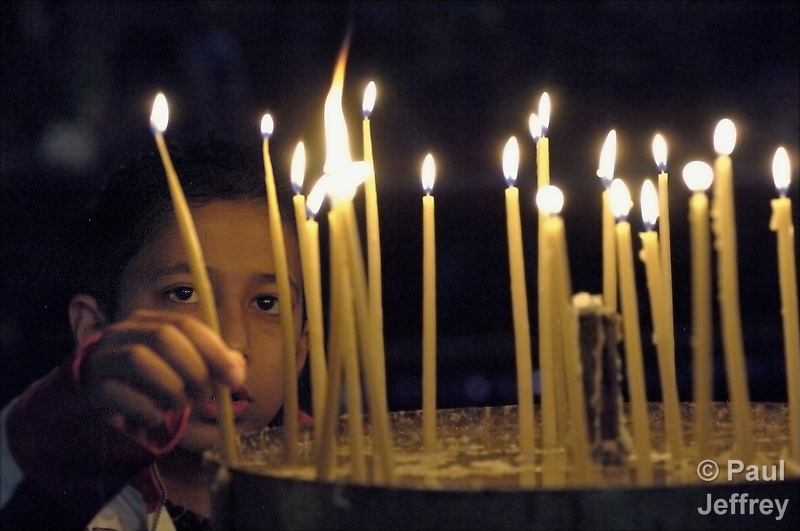 A boy lights candles in Bethlehem's Church of the Nativity, inside the occupied Palestinian West Bank. (Paul Jeffrey)