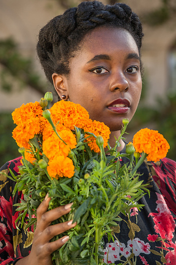 P.U.C. communication major Alexandra Smith purchases fresh cut marigolds on a beautiful morning at the Calistoga Saturday Market. (Clark James Mishler)