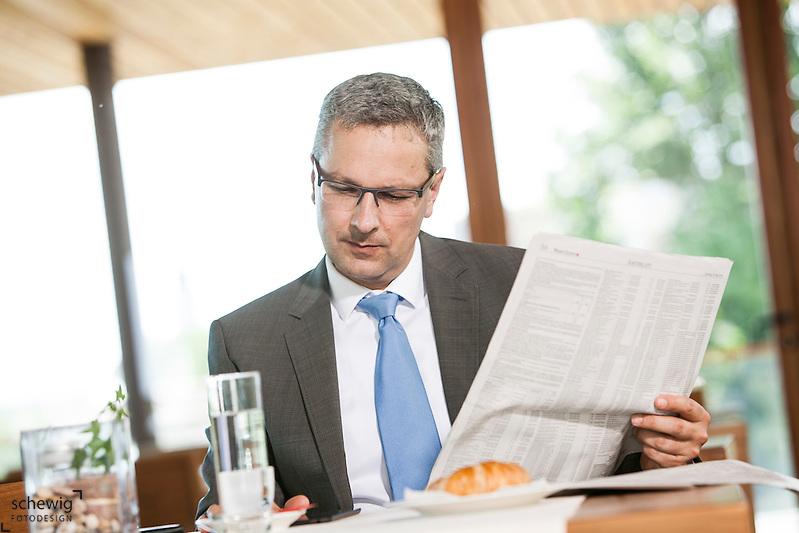 Österreich, Geschäftsmann macht Pause in Restaurant, Zeitung lesend und Tablet Computer nutzend (dieter schewig)