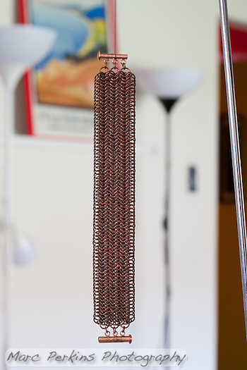 "A picture of the copper european 8-in-1 maille project seen in natural room lighting in my ""studio"".  The background has a colorful picture, lights, and other junk in it, which disappear thanks to the off-camera flashes which create an ""invisible"" black backdrop. (Marc C. Perkins)"