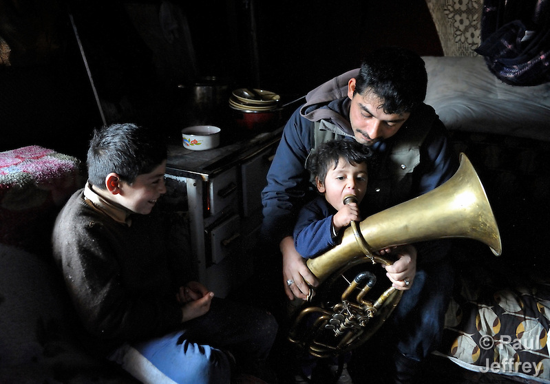 Milan Pesic gets help from one of his children as he practices his french horn inside his home in a Roma settlement in Belgrade, Serbia, in February 2012. Pesic plays in a Roma band. The families that live here, many of whom survive from recycling cardboard and other materials, are under constant threat of eviction in order to make way for new high-rise office buildings. Note: Pesic and other residents of this settlement were forcibly evicted in April 2012, two months after this photo. Many, including Pesic and his family, were relocated in metal shipping containers at the edge of the city.. (Paul Jeffrey)