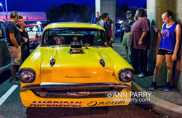 Bellmore, New York, USA. 7th August 2015. Groups of people are at yellow 1957 Chevrolet muscle car, with a blower (supercharger air compressor) sticking out through hole in hood, and American Dream written under the front grill, and parked under the elevated train tracks at the Friday Night Car Show held at the Bellmore Long Island Railroad Station Parking Lot. Hundreds of classic, antique, and custom cars were on view at the free weekly show, sponsored by the Chamber of Commerce of the Bellmores. (Ann Parry/Ann Parry, ann-parry.com)