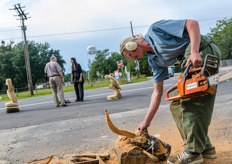 Alabama chainsaw artist James Seal carves a whooping crane as his wife, Miranda Seal, tries to sell his artwork to a bystander in Coden, Ala. The couple says they need health insurance, but they have not yet explored their options through the Obamacare health care exchange. (Photo by Carmen K. Sisson/Cloudybright) (Carmen K. Sisson/Cloudybright)