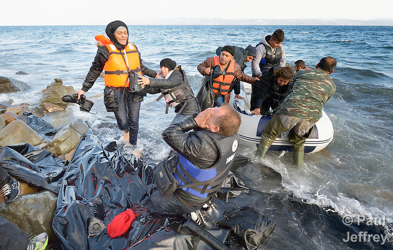 When he landed on the Greek island of Lesbos on October 30, 2015, Nabil Minas, a refugee from Syria, carried his children through the water and left them on the shore, then fell on his face and kissed the ground. A Christian, he crossed himself and covered his face with his hands, weeping with joy. The shore where he kneels is covered with the black rubber of deflated refugee boats. Minas and his family came in the boat from Turkey, paying an exorbitant amount to traffickers who provided the transport. (Paul Jeffrey)