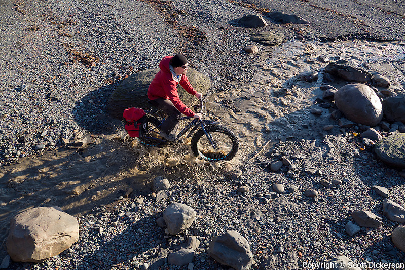 Carl Seger crosses a stream on his fat tire bike on the beach at the edge of Kachemak Bay near Homer, Alaska during an unseasonably warm winter day. (Scott Dickerson)