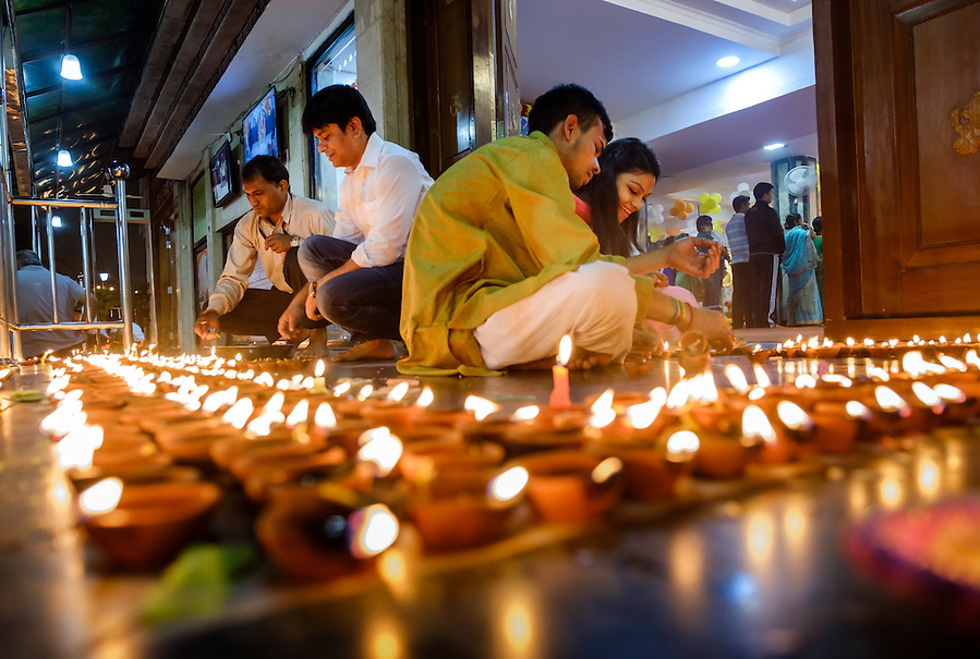NEW DELHI, INDIA - CIRCA OCTOBER 2016: People lighting candles for the Diwali celebration at the Sai Baba Temple in the Hauz Khas area of New Delhi. Diwali is also known as festival of lights, for the Hinduism, it spiritually signifies the victory of light over darkness, good over evil, knowledge over ignorance, and hope over despair. Its celebration includes millions of lights shining on housetops, outside doors and windows, around temples and other buildings in the communities. (Daniel Korzeniewski)