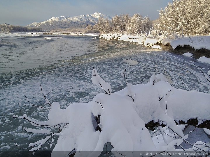 Ice forms on the Chilkat River in the Alaska Chilkat Bald Eagle Preserve near Haines, Alaska. In the background is Four Winds Mountain. SPECIAL NOTE: iPhone photo (John L. Dengler)