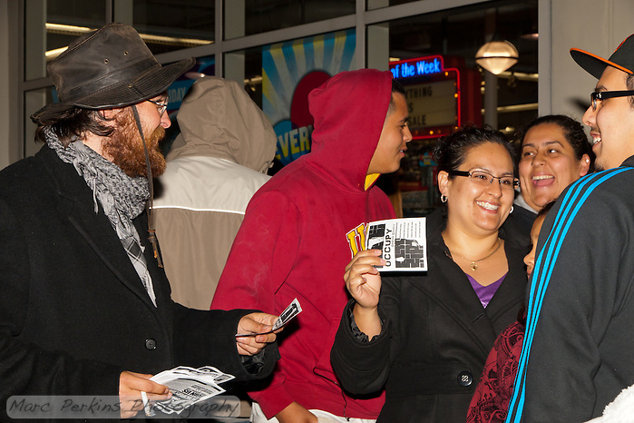 Justin H., an Occupy Orange County, Irvine protestor, hands out fliers to customers lined up at the Old Navy at South Coast Plaza early in the morning (12:48am) on Black Friday. (Marc C. Perkins)