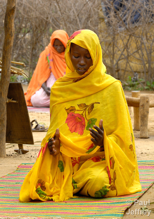 Farmah Adam Ibrahim (right) and Sit-Eldoma Atiya (back left) pray outside their hut in the Bilel Camp for internally displaced persons in Sudan's war-torn Darfur province. Most of Darfur's residents are Muslims. A government sanctioned ethnic war has killed more than 400,000 people and left some 2.5 million displaced since 2003. (Paul Jeffrey)