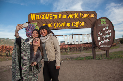 "College student friends:  Enka, Lores and Lizbeth snap a ""selfie"" near Calistoga while in front of the single most photographed sign in the Northern California,  enka@gmail.com (© Clark James Mishler)"
