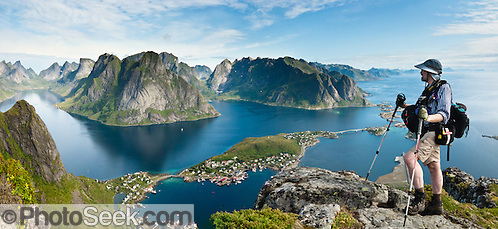 Above the Arctic Circle, ascend a slippery steep trail to Reinebringen for spectacular views of Reine village, highway E10, and sharply glaciated peaks surrounding Reinefjord, on Moskenesøya (the Moskenes Island), Lofoten archipelago, Nordland county, Norway. Panorama stitched from 3 overlapping photos. (© Carol Dempsey / PhotoSeek.com)