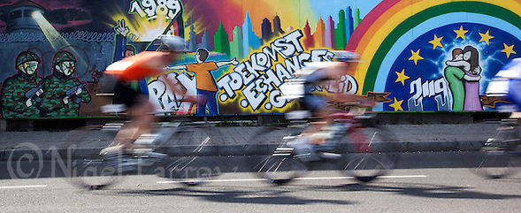 22 MAY 2011 - DUNKERQUE, FRA - Competitors race past a mural celebrating the fall of the Berlin Wall during the Triathlon de Dunkerque (PHOTO (C) NIGEL FARROW) (NIGEL FARROW/(C) 2011 NIGEL FARROW)