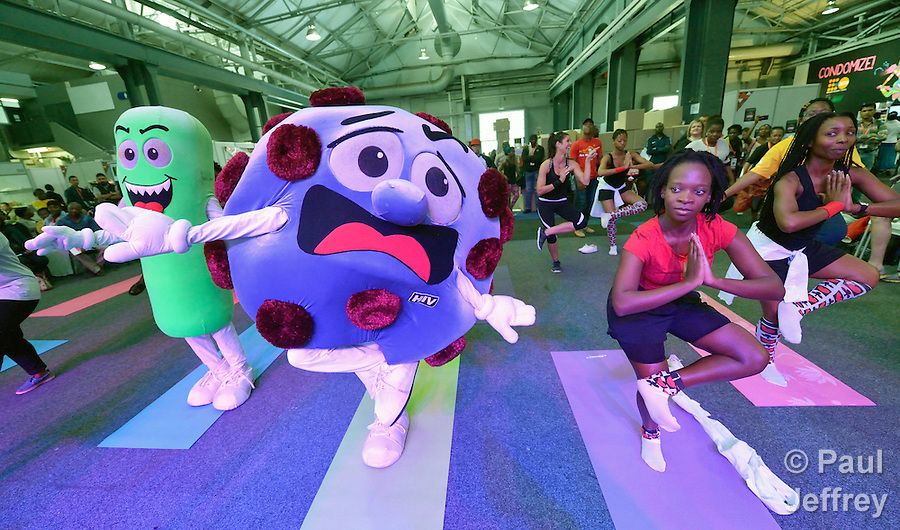 Mascots representing TB and HIV, which are often fatal when they get together, join in an aerobics session in the Global Village at the 2016 International AIDS Conference in Durban. (Paul Jeffrey)