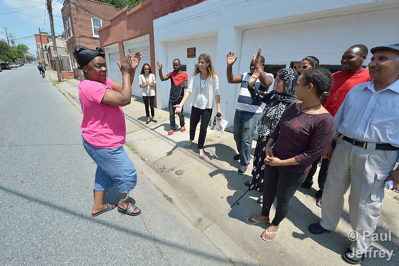 "As members of a cultural orientation class for newly arrived refugees walked together on a street in downtown Lancaster, Pennsylvania, the woman on the left came out of her home and crossed the street, clapping her hands and repeating, ""Welcome to America!"" The class was sponsored by Church World Service. Photo by Paul Jeffrey for Church World Service. (Paul Jeffrey)"