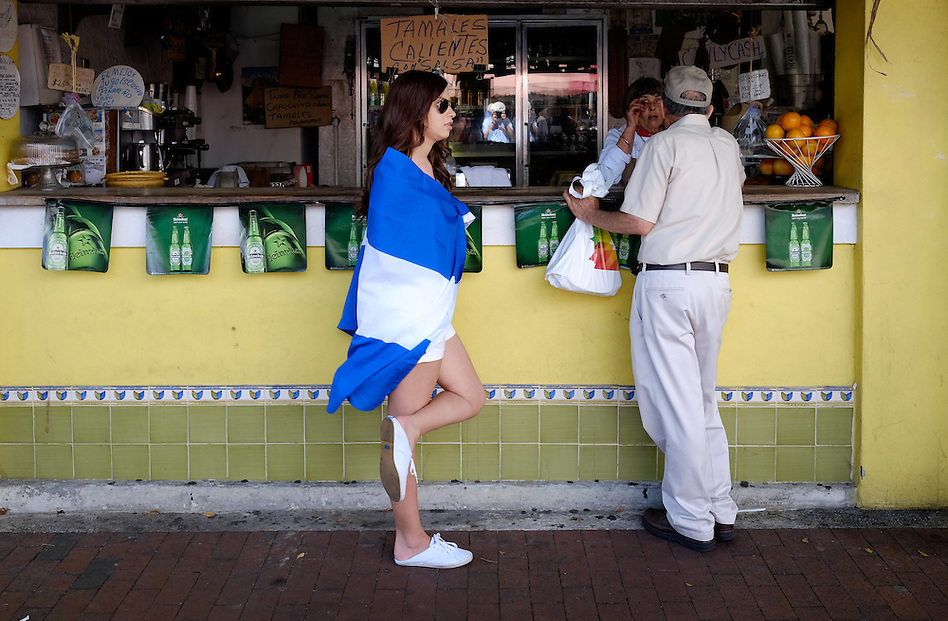 MIAMI - MARCH 9, 2014: Woman wearing a flag during the the 37th Calle Ocho festival, an annual event that takes place over Eighth Street in Little Havana featuring plenty of music, food, and  it is the biggest party in town that celebrates hispanic heritage. (Daniel Korzeniewski)