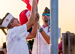 VFW Post 8967 members C.D. McGabe, chief of staff, and Jason Jenkins, senior vice post commander, lower the American and Texas flags at sunset, Aug. 25, 2018, at Roberts Point in Port Aransas, Texas. The ceremony was part of a commemoration marking the one-year anniversary of Hurricane Harvey, which heavily damaged the seaside community in 2017. Community members placed 2,300 luminaries around the park as a way of thanking those who helped in their time of need. (Photo by Carmen K. Sisson) (Carmen K. Sisson/Cloudybright)