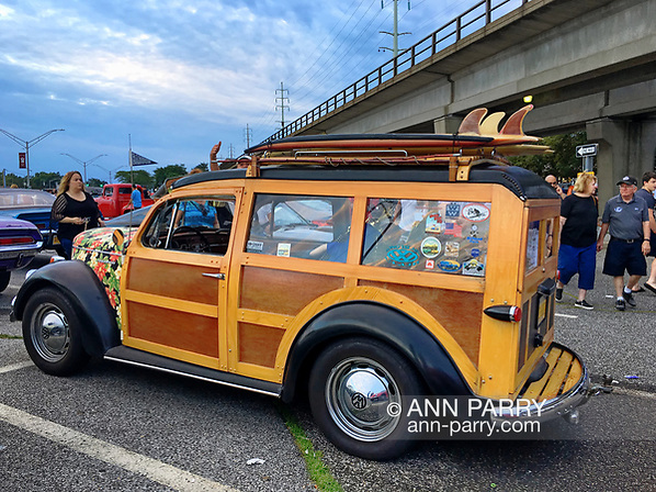 Bellmore, New York, USA. 11th August 2017. At Bellmore Friday Night Car Show, MIKE RADOMSKI, of Valley Stream, is the owner of Wunderbug Woody Volkswagen, with homemade angel hood ornament. Elevated tracks of Bellmore Long Island Rail Road station are seen in background. (Ann Parry/Ann Parry, ann-parry.com)
