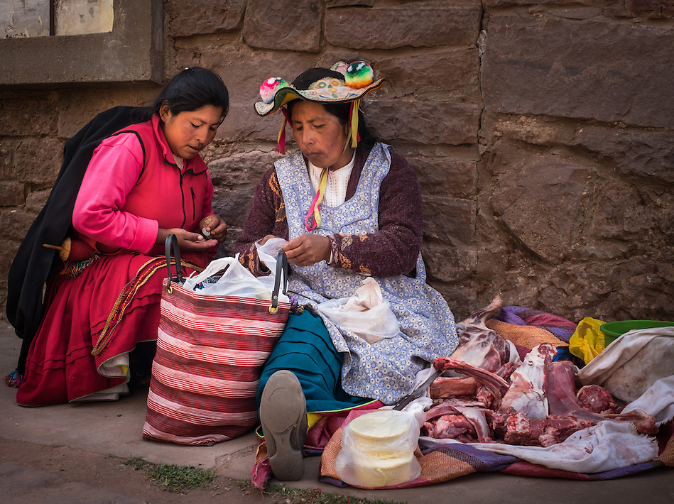 TAQUILE, PERU - CIRCA OCTOBER 2015: Woman purchasing meat in the market of Taquile in Lake Titicaca. (Daniel Korzeniewski)