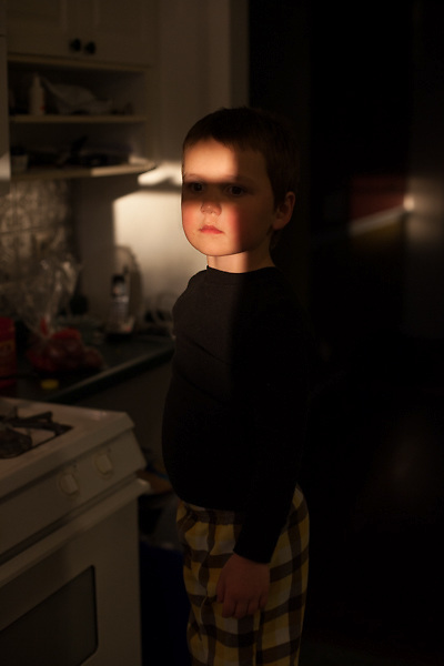 My younger son stands on a kitchen stool, threatening to turn off the microwave timer because he doesn't want to have a time-out. (Kristen Schmid)