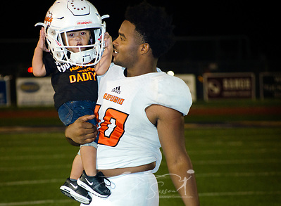 Refugio High School running back Jacobe Avery carries his son, Kameron Avery, off the football field, Sept. 29, 2017, in Seguin, Texas. Football is a big part of life in Refugio, and Mr. Avery hopes his son will someday play for the team. (Photo by Carmen K. Sisson) (Carmen K. Sisson/Cloudybright)
