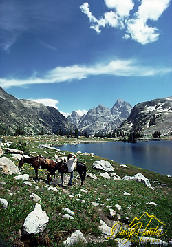 Horseback rider takes in the view of Lake solitude and the Grand Teton from the Teton backcountry