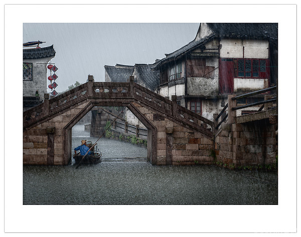A boatman takes shelter from the torrential rain in Xitang, Zhejiang, China (Ian Mylam/ Ian Mylam (www.ianmylam.com))