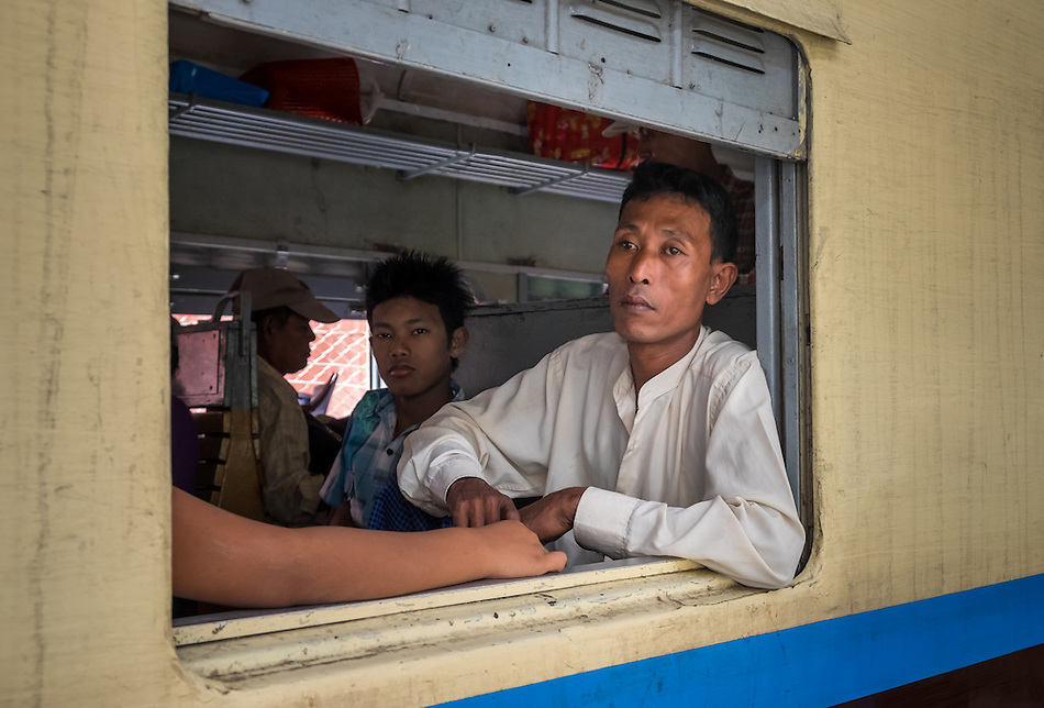YANGON, MYANMAR - CIRCA DECEMBER 2013: Burmese man looking away from a train window while it waits for departure in Yangon Central Railway Station (Daniel Korzeniewski)