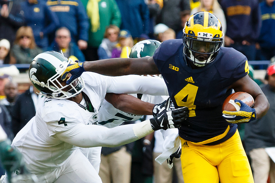 Oct 17, 2015; Ann Arbor, MI, USA; Michigan Wolverines running back De'Veon Smith (4) rushes past Michigan State Spartans defensive lineman Malik McDowell (4) at Michigan Stadium. Mandatory Credit: Rick Osentoski-USA TODAY Sports (Rick Osentoski/Rick Osentoski-USA TODAY Sports)