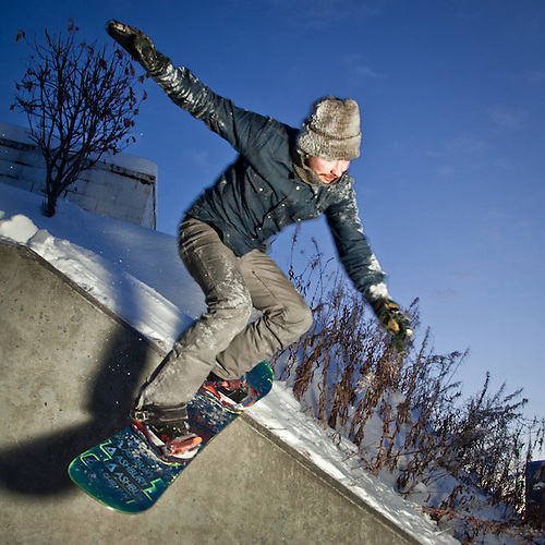 Urban snowboarder, Guss Engle, performs a Wallie Nose Glide Pretzel on the 5th Avenue Hill across from Elderberry Park, downtown Anchorage (Clark James Mishler)