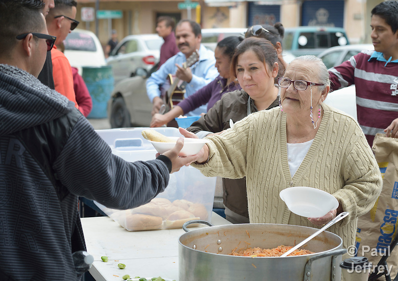 "Maria Natividad Granados, a Methodist woman in Nuevo Laredo, Mexico, serves food to Cuban immigrants in that city's Plaza Benito Juarez on March 3, 2017. Hundreds of Cubans are stuck in the border city, caught in limbo by the elimination in January of the infamous ""wet foot, dry foot"" policy of the United States. They are not allowed to enter the U.S. yet don't want to return to Cuba. Many of the city's churches have become temporary shelters for the immigrants, and congregations rotate responsibility for feeding the Cubans, who have slowly been forced to appreciate Mexican cuisine. Such solidarity from ordinary Mexicans is being tested these days, as not only are the Cubans stuck at the border, but the U.S. has stepped up deportations of Mexican nationals, while at the same time detaining many undocumented workers from other nations and simply dumping them on the US-Mexico border. Granados is a member of the El Ebenezer Methodist Church in Nuevo Laredo. (Paul Jeffrey)"