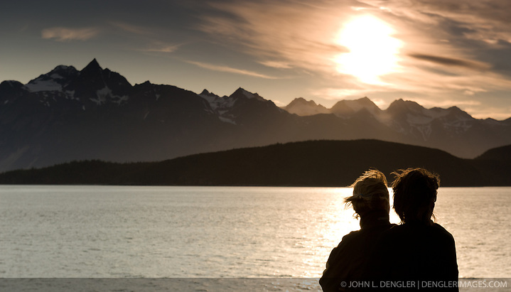 Unidentified passengers on the Alaska Marine Highway System ferry m/v Malaspina enjoy the scenery of the Lynn Canal as the sun sets behind the Chilkat Range near Haines, Alaska. (John L. Dengler)