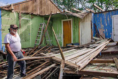 Joe Guerra talks to a neighbor as he clears rubble from his storm-damaged home, Oct. 4, 2017, in Refugio, Texas. Refugio was hard-hit by Hurricane Harvey in late August and continues to recover. Many homeowners, like Mr. Guerra, experienced so much damage that they will have to demolish their homes and rebuild. (Photo by Carmen K. Sisson) (Carmen K. Sisson/Cloudybright)