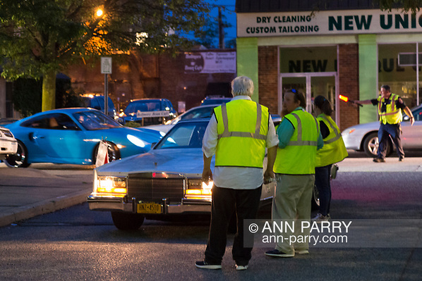 Bellmore, New York, USA. August 11, 2017. Members of the Chamber of Commerce of the Bellmores and Nassau County Auxiliary Police wear yellow neon reflective safety vests as they guide cars into the main lot of the Long Island Rail Road Bellmore Train Station parking lot where the Bellmore Friday Night Car Show is held. (Ann Parry/Ann Parry, ann-parry.com)