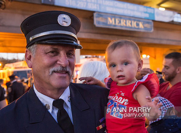 Merrick, New York, USA. 11th September 2015. RILEY E. GIES, one-year-old granddaughter of Fire Chief Ronnie E Gies who died responding to 9/11 NYC Terrorist Attack, is held by CRAIG MALTZ, a Bellmore volunteer firefighter, after Merrick Memorial Ceremony for Merrick volunteer firefighters and residents who died due to 9/11 terrorist attack at NYC Twin Towers. Ex-Chief Ronnie E. Gies of Merrick F.D. and FDNY Squad 288, and Ex-Captain Brian E. Sweeney, of Merrick F.D. and FDNY Rescue 1, died responding to the attacks on September 11, 2001. (Ann Parry/Ann Parry, ann-parry.com)