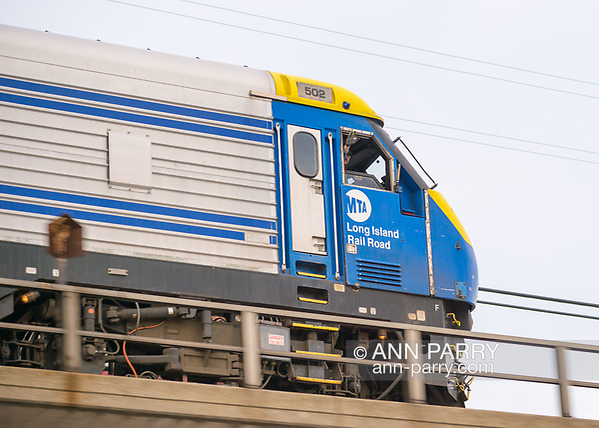 Bellmore, New York, USA. 11th August 2017. Train engineer waves his hand out window of MTA Long Island Rail Road train front car, as train speeds on overpass above station parking where Bellmore Friday Night Car Show is held. (Ann Parry/Ann Parry, ann-parry.com)