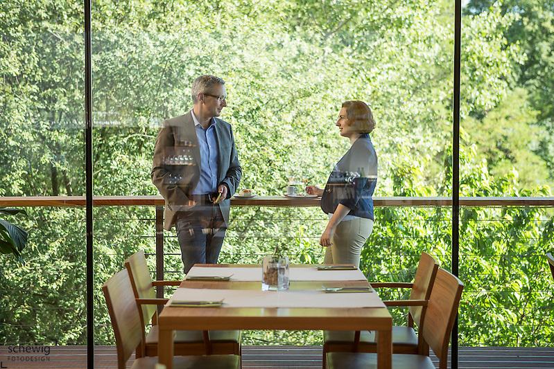 Österreich, Geschäftsmann und Geschäftsfrau vor Restaurant, Kaffeepause, nach dem Meeting, informelle Konversation, entspannte Atmosphäre, Blickrichtung von innen nach außen (dieter schewig)