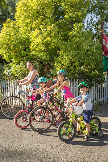 """We lived in Santa Rosa and had to get in the car to go anywhere.  Now that we live in Calistoga, we ride our bikes everywhere.""  -Para-Special Ed instuctor Melinda Mendoza with her kids: Nataline, Emily, and Anthony, in front of their home on Grant Street in Calistoga. (Clark James Mishler)"