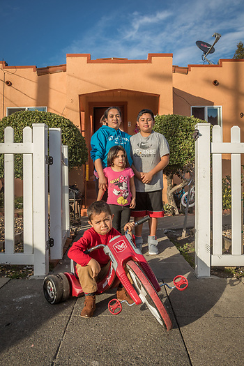 House keeper Nereida Apalinar with her kids, Javier (12) and Elizabeth (4) and next door neighbor Kevin Vega (front) in front of their home on Washington Street in Calistoga (©2017 Clark James Mishler)