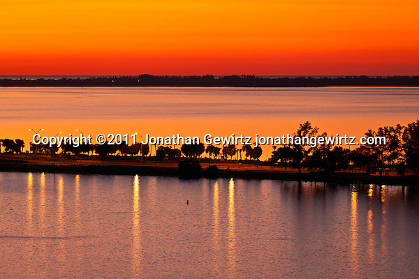 Red twilight immediately before sunrise, looking over Miami's Rickenbacker Causeway and Key Biscayne toward the Atlantic Ocean on New Year's Eve 2011. (© Jonathan Gewirtz)