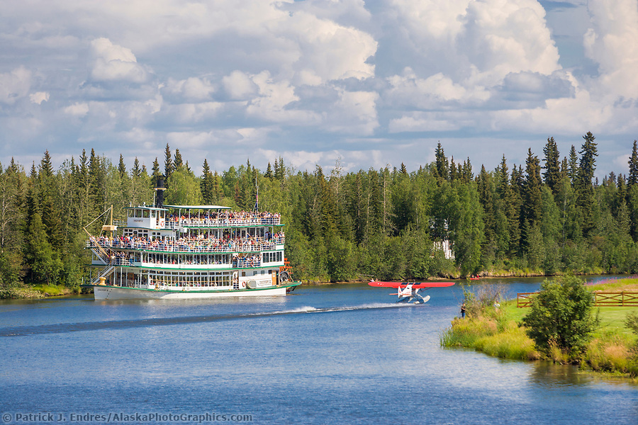 Alaska tourism photos: Riverboat Discovery sternwheeler with tourists, bush plane on floats takes off from the Chena River, Fairbanks, Alaska. (Patrick J. Endres / AlaskaPhotoGraphics.com)
