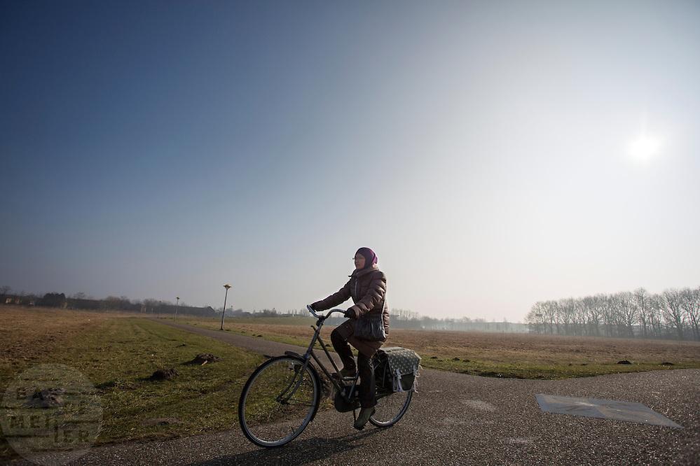 In Lelystad rijdt een vrouw op de fiets door het polderlandschap.