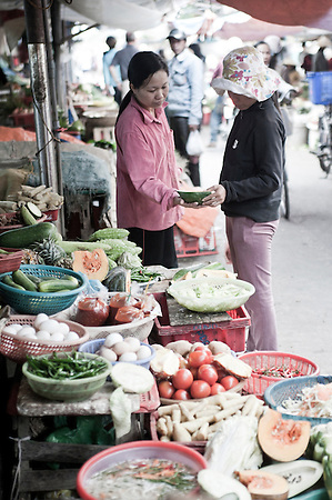Women Bartering at Hoi An Market, Vietnam. The crowded streets and stalls are full to bursting point with locals buying and selling fruit, vegetables, fresh fish and hand-made crafts. It is a great place to spend an afternoon exploring, trying traditional Vietnamese foods, chatting the market stall owners and learning the art of bartering. No matter how hard you try you will NEVER get anything for the same price as the locals!