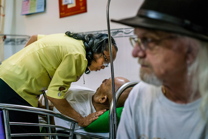 MY LUONG, VIETNAM - JANUARY 9: Nguyen Thi Hanh cares for her husband of thirty nine years who was bed ridden by a stroke eight years prior, as Jim Reischl, Hanh's former boyfriend during the Vietnam War looks on. (Quinn Ryan Mattingly)
