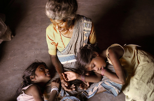 Vijyashree (left, age 7) and Vijitha Viswanathan (age 9) with their maternal grandmother Govindammal (age 70) at her home in the Pudhupattinam tsunami temporary relief camp. These photographs encompass four years in the lives of two families of children from South India who lost their mothers to the Asian tsunami. Following that momentous event in 2004, the five Krishnamurthy sisters from Puddupettai went to live in the Cuddalore Government Special Home for Tsunami Children. And Vijitha and Vijyashree Viswanathan, after an initial brief spell at the same home, now live with their father and his new wife in the nearby fishing village of Thalanguda.  Each child affected by the tsunami had to adapt to changed circumstances and cope with emotions no one in their family could have possibly anticipated. The younger children seemed to adjust more quickly than their older siblings. And, while grief rendered some silent, in others it provoked a real sense of anger. Some became withdrawn while others craved attention and resorted to disruptive behavior. For all of the children, the experience of losing a parent seemed to strengthen the bond they shared with their brothers and sisters.  The loss of a parent meant that some of the children photographed in this project inherited responsibilities that, while often a burden, provided a distraction from their own painful emotions. Sivaranjini Krishnamurthy lost her mother to the tsunami and then, together with her four younger sisters was abandoned by her father. At eleven years of age she took on the role of a mother to her younger sisters. Though she attends school and receives the support of orphanage staff, Sivaranjini has sacrificed much of her own childhood to take care of them.  For Sivaranjini and the other children whose experiences are presented here, the tsunami is a defining event in their lives; the terrible personal upheaval they have suffered will inevitably shape all of their futures.  Photo: Tom Pietrasik Tami (Tom Pietrasik)