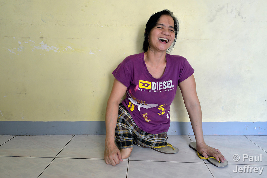 In Abucay, a seaside town in the Philippines province of Bataan, Ellen Bundang laughs as she sits on the floor of her home. Born with abnormal legs, she is a member of the local Persons with Disabilities (PWD) organization. (Paul Jeffrey)